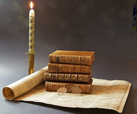 enlightened: old books and map of 17 th century, enlightened in the candle