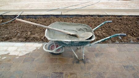 public works: wheelbarrow filled with cement, construction site of public works Stock Photo
