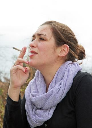 屋外での女性の喫煙タバコ 写真素材