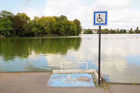 Place pour fauteuil roulant, en face d'un étang. Banque d'images - 31398987
