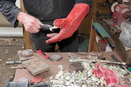 Manufacturing of small pewter objects, craftsman working in front of the public Stock Photo