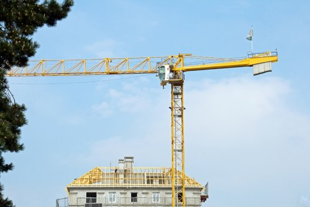 tree works: House under construction and yellow crane, roof under construction Stock Photo