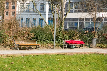 sleeping bag: person sleeping in a sleeping bag on a bench. Poverty and loneliness in the city (France)