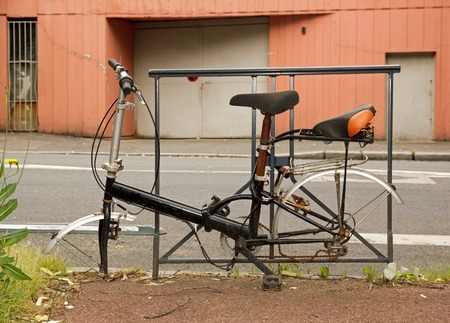 Vélo abandonné sur la route, roues démontées. Vélo sans roues attachées à une porte de la ville Banque d'images