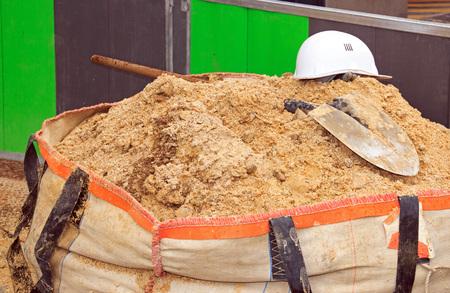 Bag of sand, shovel and helmet, break work on site construction Stock Photo
