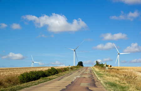 Small country road and wind turbines (Yonne, Burgundy, France) Stock Photo