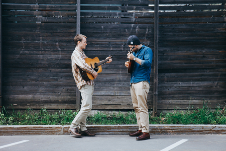 Two hipster musicians play the guitars on the street.