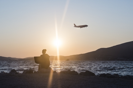 Silhouette of woman with laptop, working at the beach  Airplane in the background