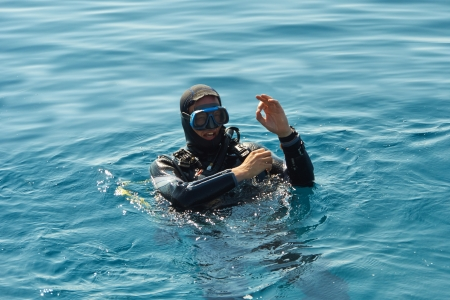 a diver is showing the ok sign with his hand and waiting to get under water
