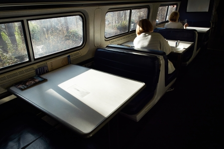 Adult train passangers reading at table while riding the East Coast Train between Boston and New York