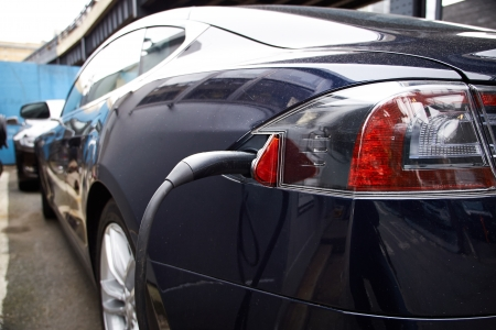 A Tesla Motors Model S charging at a public parking garage.