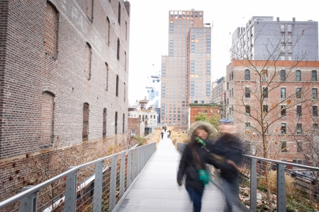 People relaxing and strolling on The High Line. The High Line is a recently created New York City park located on what used to be an elevated industrial railroad line. It is located in the meatpacking district on the west side of Manhattan. It stretches f