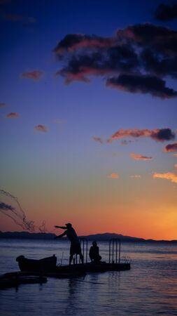 red: Neto de lanzamiento Pescador con la puesta de sol Foto de archivo