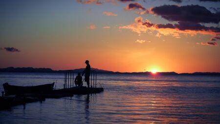 red: Pescador con la puesta de sol en la isla del Caribe Foto de archivo