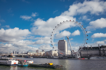 Beautiful day with cumulus clouds overlooking river thames and London eye