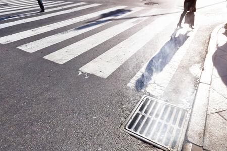 pedestrians cross zebra stripes in Manhattan on a cold but sunny winter day photo