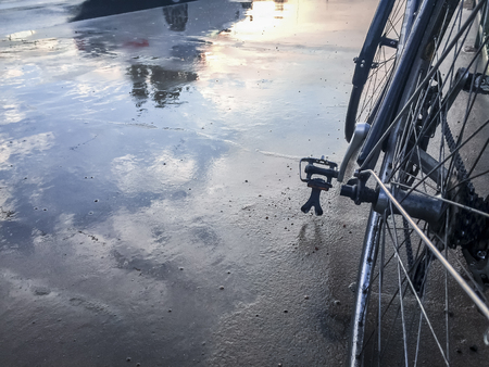 Wet street with reflections and bicycle