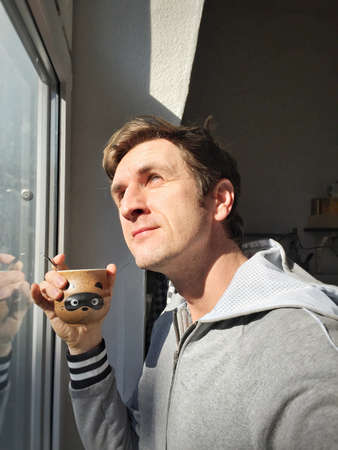 casual: Young Caucasian man in casual drinking hot coffee next to window