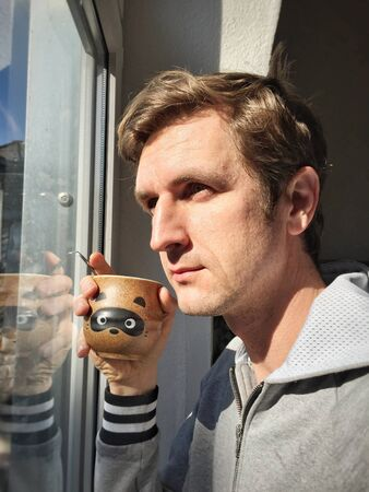 man: Young Caucasian man in casual drinking hot coffee next to window