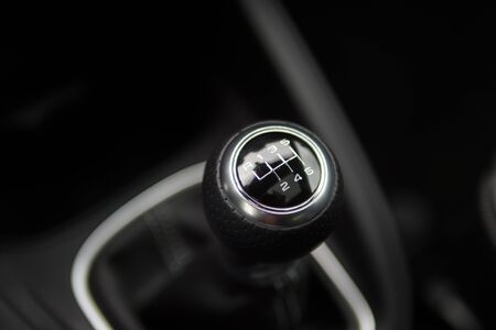 gearstick: Close up of a manual shifter in a new car. The shifter is black and silver and made of leather.