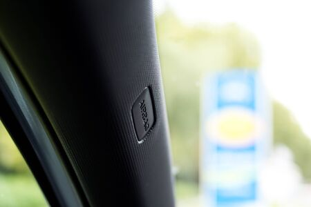 style advice: Detailed view of a part in the car. The material is black and has pattern. There is the advice airbag written and the backround is blurred with different colors.