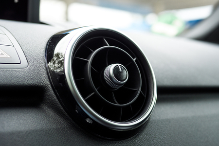 Close up of a round and black car ventilation. On the left side is the button hazards. The ventilation is cased is black and silver material vanish.
