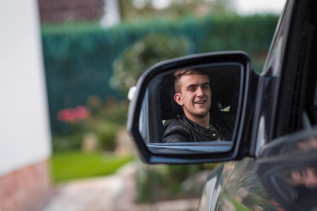 licence: happy young blonde adult inside of a car. happy to have his new licence. Stock Photo
