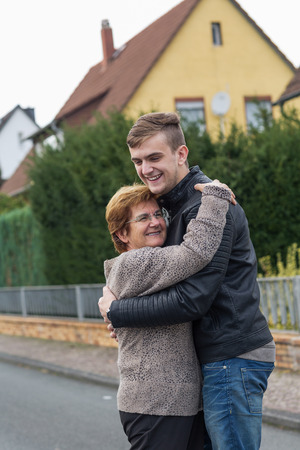 cuddle: teenager hugging his grandmother on street. happy and proud woman cuddle her grandson. Stock Photo