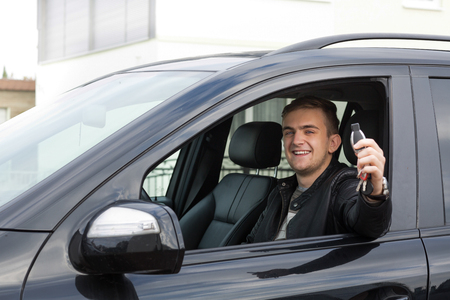 licence: happy young adult holding car keys in his hand and celebrating his new licence.