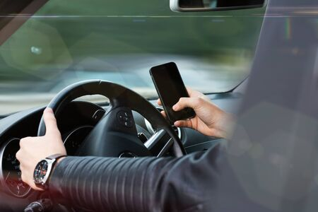 distraction: young man holding a smartphone while driving. dangerous travel situation with distraction from street Stock Photo