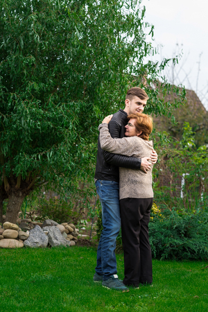 cuddle: teenager hugging his grandmother in garden. happy and proud woman cuddle her grandson.