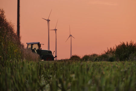 wind down: A Tractor crossing the scenery of a field of mowed down straws of wheat and some wind tubines in the background under a red sky