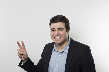 smirk: Dark-haired european businessman with a smirk makes a peace sign while in front of a gradient background Stock Photo
