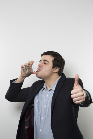 perky: Dark-haired european businessman with a perky look gives a thumps-up while drinking from a glas of water in the other hand while in front of a gradient background