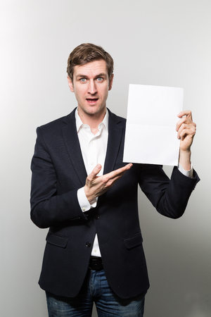 Blond-haired european businessman shows something on a piece of paper with a incredulous face while in front of a gradient background