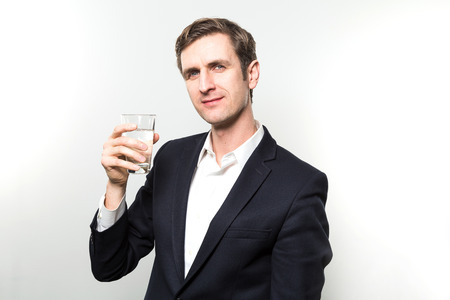 Blond-haired european businessman after drinking from a glas of sparkling water with a satisfied look in front of a gradient background