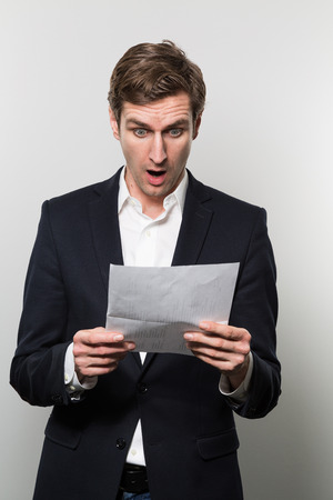 Blond-haired european businessman with a scared look stares at a piece of paper with bad news on it while in front of a gradient background