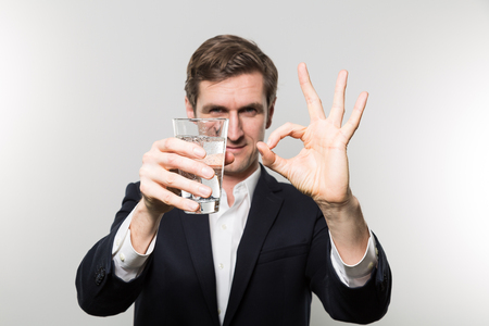 Blond-haired european businessman holding a glas of sparkling water with a satisfied look and giving a O.K. sign in front of a gradient background Stock Photo