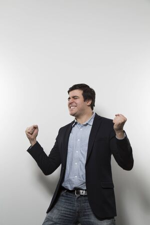 Dark-haired european businessman clenching his fists in a victory dance while in front of a gradient background with a grin Stock Photo