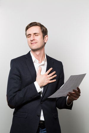 Blond-haired businessman puts his hand on his chest and feels a sigh of relief while in front of a gradient background Stock Photo