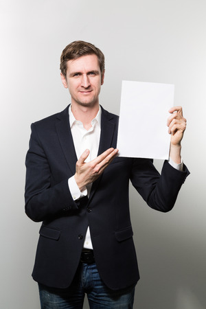 amiable: Blond-haired european businessman shows something on a piece of paper with a amiable face while in front of a gradient background Stock Photo