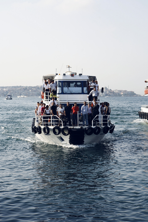disembark: A little ferry boat prepares to moor on the riverbank of the Bosphorus with a dozen people waiting to disembark in Istanbul, Turkey
