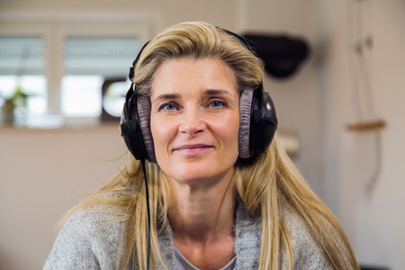 Shaking up time! close-up ofhHappy middle-aged woman listening to a track on headphones in modern apartment