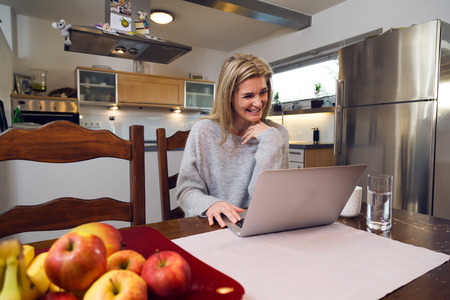 Housewife sitting at her kitchen table drinking coffee while working at her laptop. Her facial expression is happy and cheerful.