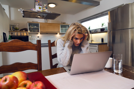 Woman seated at a table looking at her laptop screen in consternation and horror