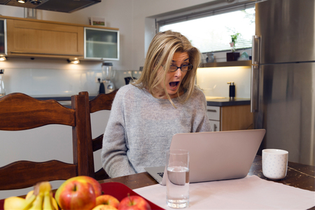 Woman seated at a table looking at her laptop screen in consternation and surprise. She is shocked about news read on laptop 版權商用圖片