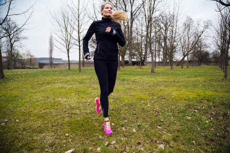 attractive middle aged blonde woman running in park in between trees. cold winter day with exercises outdoors Reklamní fotografie
