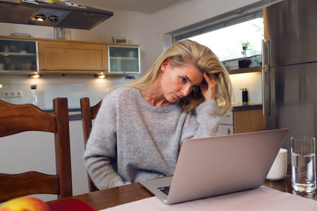 Woman seated at a table looking at her laptop screen in consternation