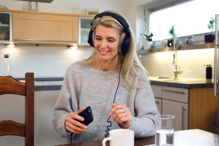 Portrait of relaxed middle-aged woman with headphones sitting at kitchen table and listening music on smartphone. Cup of coffee and glass of water in the foreground