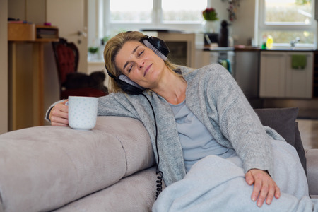 Middle-aged woman drinking coffee, relaxing on couch, wearing headphones at home and enjoying her music. Kitchen area in the background.